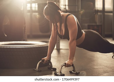 Young woman does push-ups with sports equipment in the gym. Real Workout Candid fitness Girl