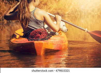 Young woman and dog in canoe on river at sunset with paddle