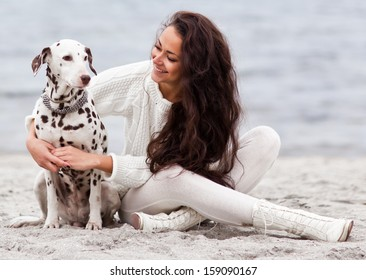 young woman with dog on the beach