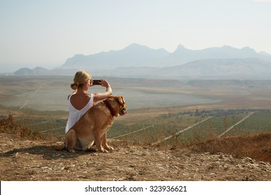 Young woman with dog on a sunny day sitting in high mountains and take a picture on smartphone.