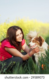 Young woman with dog outside.