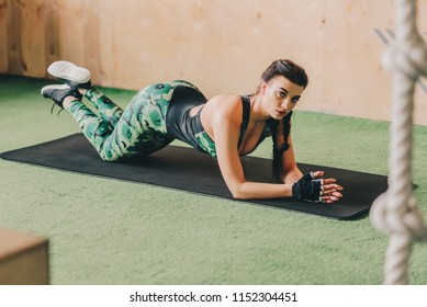 Young woman doing abs workout in a gym on a mat. Fitness, sport, training, gym and lifestyle concept. Copyspace