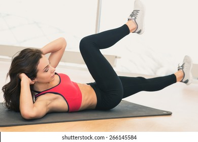 Young woman doing abs workout in a gym on a mat. Sport and lifestyle concept.