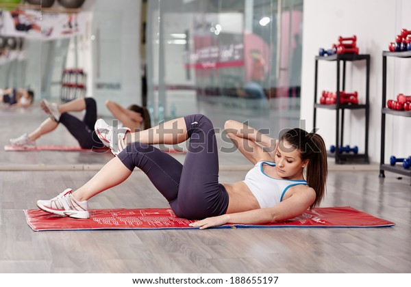 Young woman doing abs workout in a gym on a mat