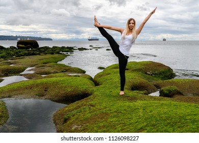 Young woman doing acrobatic exercises at the intertidal zone of Stanley Park in Vancouver, British Columbia.