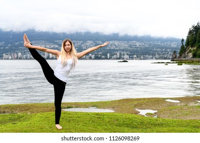 Young woman doing acrobatic exercises at the intertidal zone of Stanley Park in Vancouver, British Columbia. There is a hillside and city of Vancouver in the background.