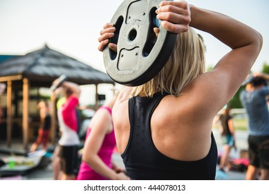 Young woman doing back exercises. Bodypump workout outdoor.