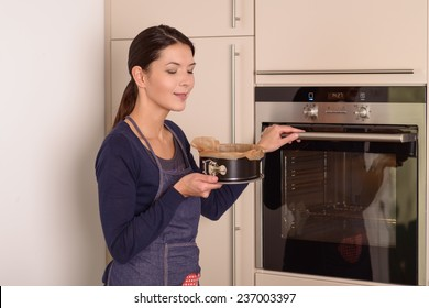 Young woman doing baking at home placing a cake in the oven to cook reaching out with her hand to open the oven door while holding a baking tin