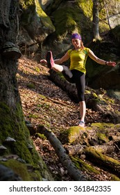 young woman doing balance fitness exercise before running in the nature spring forest