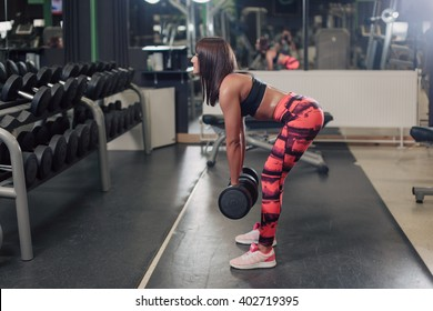 Young woman doing bent over hamstring exercises with dumbbells at the gym in front of the dumbbell rack