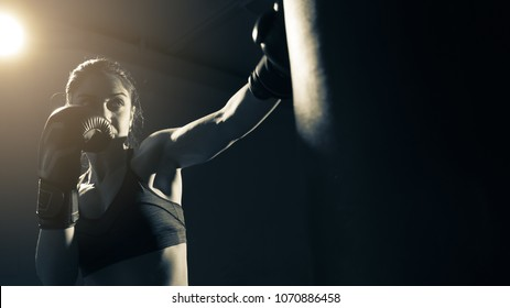 Young woman doing boxing training at the gym, she is wearing boxing gloves and hitting the punching bag