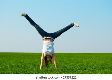 young woman doing cartwheel at the green meadow
