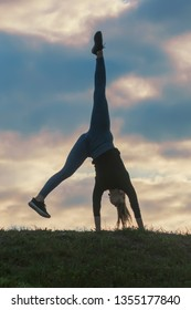 Young woman doing cartwheel on the grass Morning workout beautiful sunrise