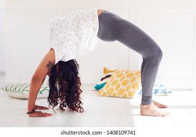 young woman doing Chakrasana Yoga (Full Wheel Pose) at home
