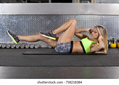 Young woman doing chunches on floor at gym