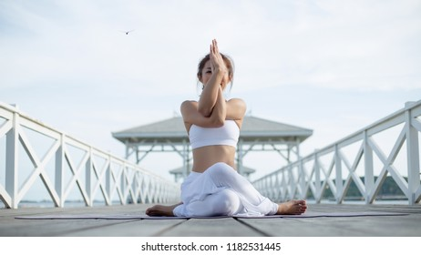 Young woman doing complex yoga exercise sitting in Garudasana arms exercise eagle pose. Amazing yoga landscape in beautiful sky and enjoying sea view on wooden floor, concept for exercising