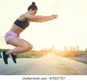 Young woman doing crossfit exercises outdoors jumping up onto a low stone wall at the side of a rural road or promenade with raised arms, side view with cityscape in the rising sun