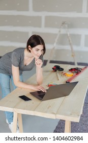 Young woman doing DIY renovations at home leaning on a temporary work table working on a laptop computer surrounded by tools