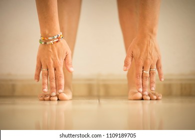 young woman doing exercise at home stretching touching feet with hands fingers. defocused image with focus on touch point. exercise indoor yoga pilates to build a healthy nice body