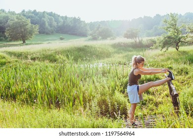 Young woman doing exercise in the nature at sunset