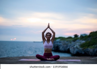 Young woman doing exercise yoga. sitting in Sukhasana exercise, Easy Seat pose pose. Amazing yoga landscape in beautiful sky and enjoying sea view with evening, concept for exercising, health care
