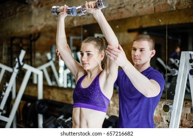 Young woman doing exercises with dumbbells in the gym with a personal trainer
