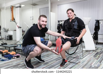 Young woman doing exercises in electrical muscular stimulation suit with her personal trainer at rehabilitation center.