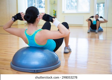 young woman doing exercises on bosu ball in gym