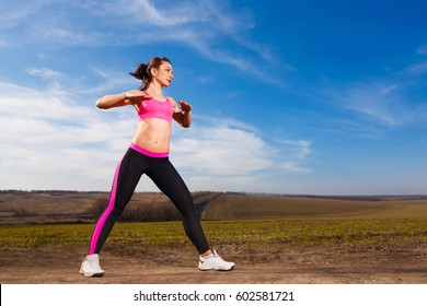 young woman doing exercises on blue sky background in countryside