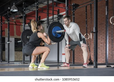 Young woman doing exercising with weight while her trainer looks on