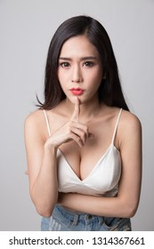 Young woman doing finger on lips.
