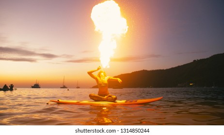 Young woman doing fireshow fire breathing perforrmance on sup board with paddle at sunset.