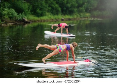 Young woman doing fitness on a board with an oar.