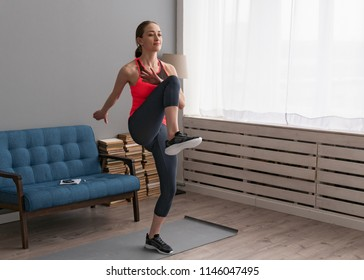 Young woman doing fitness training at home and walking high knees