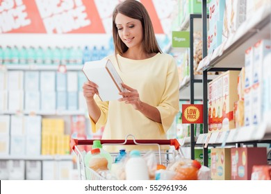 Young woman doing grocery shopping at the supermarket and reading food labels with ingredients on a box, shopping and nutrition concept