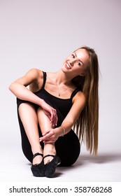 Young woman doing gymnastic exercise on white isolated background.Tenderness, grace, melody and plastic of gymnastic girl with crossed legs in thinking position.