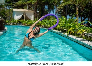 Young woman doing gymnastics in the outdoor pool using a swimming noodle.