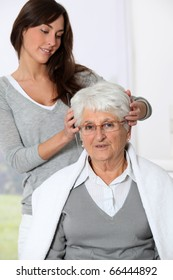 Young woman doing an haircut to old woman