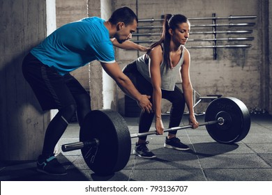 Young woman doing hard exercise at the gym with a coach.
