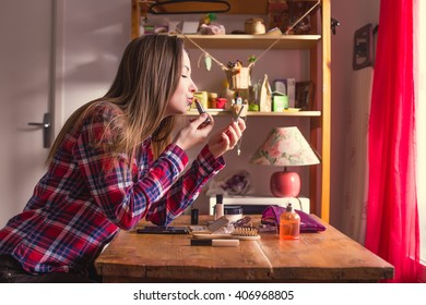 Young woman doing her makeup at the table at home and paints her lips with lipstick