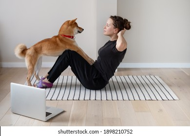 Young woman doing home strength training together with the help of her dog using online lesson