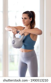 Young woman doing home workout with kettlebell.