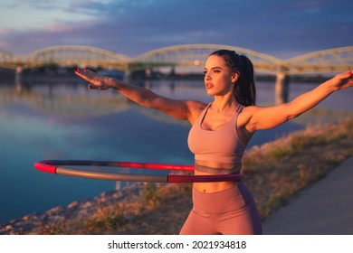 Young woman doing hula hoop exercise at riverside in sunset