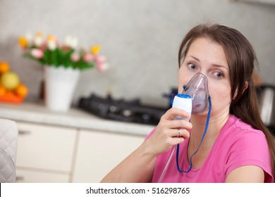Young woman doing inhalation with a nebulizer at home