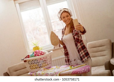 Young woman doing ironing clothes at home and making selfie