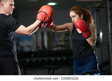 Young woman doing kickboxing training with her coach. Woman fighter ready to throw a punch with trainer teacher holding pads for boxing session