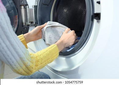 Young woman doing laundry in laundromat