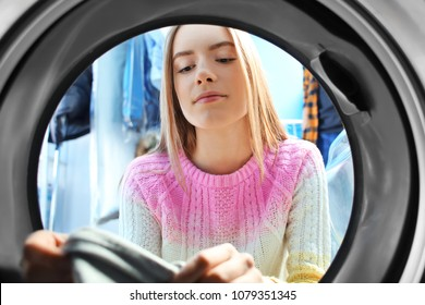 Young woman doing laundry in laundromat, view from the inside of washing machine
