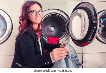 Young woman doing laundry in laundromat shop - Smiling girl laundering and looking up - Concept of daily housework and alternative ways to save time and energy