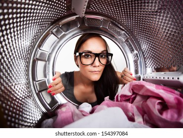 Young woman doing laundry View from the inside of washing machine.